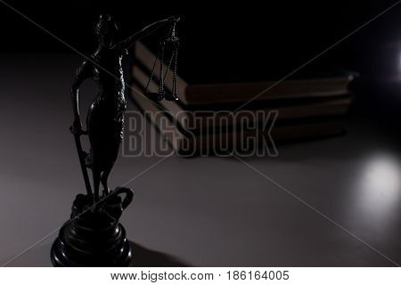 Silhouette of Themis on a white table against the background of the books.