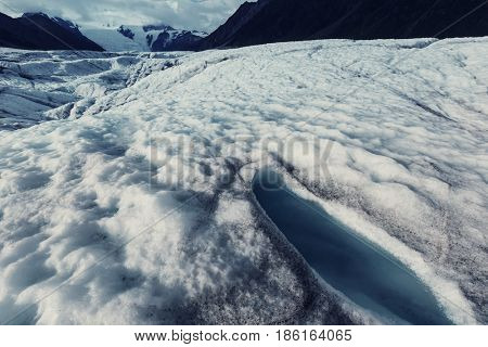 Man hiking with crampins across the Kennicott glacier in the Wrangell-St. Elias National Park, Alaska