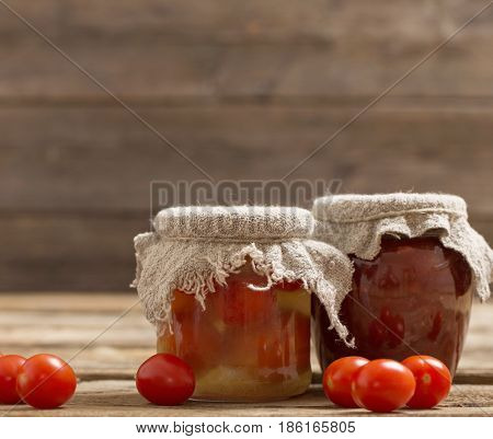 Fresh tomatoes and tomato sauce on wooden background