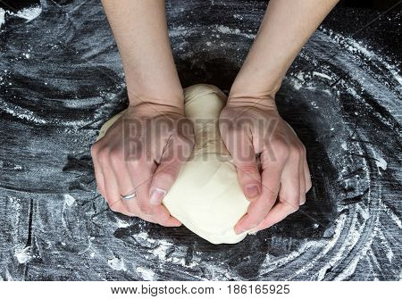 yeast dough is kneaded by women on dark wooden table