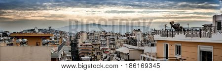 Panoramic view of sunset over the roofs in the city of Piraeus port in Greece