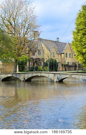 view of houses along walking bridge over the water in Bourton On The Water England a famous toursist destination in England