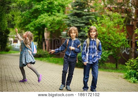 Three little friends hurry on lessons in school. The schoolgirl has noticed something on a tree. Boys smile.