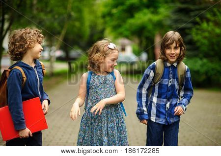 Little school students have started a game on the schoolyard. Two boys and the girl have fun waiting for the beginning of occupations. Fine morning.