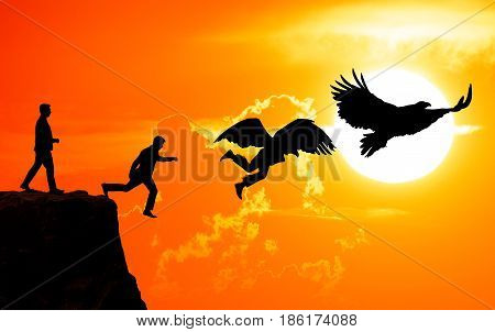 The concept of freedom. A man jumps from a rock and transforms into a bird against the background of a sunset. The concept of success.