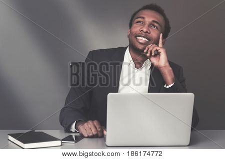 Portrait of a young African American businessman sitting at his workplace and dreaming of success. Toned image