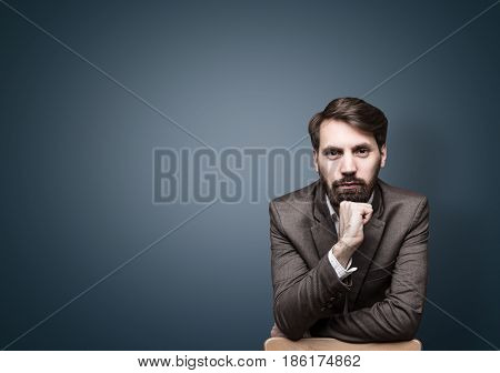 Portrait of a serious bearded businessman wearing a brown suit and leaning on a chair near a black wall. He is looking at the viewer and portraying confidence. Mock up