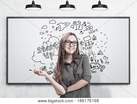 Portrait of young woman wearing glasses holding a marker and standing near a whiteboard with a start up sketch