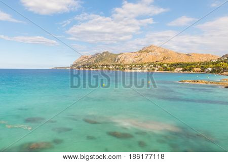 Crystal clear water at seaside in Mallorca long exposure with clouds on the sky and mountains on background. Summer tourism and travel concepts.