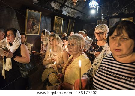 Bethlehem Israel May 8 2017: Pilgrims praying with candles into the crypt in Nativity Church in Bethlehem in Palestinian Autonomy.