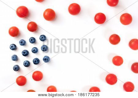 Closeup of cherry tomatoes and blueberries on white, forming frame for copy space. Culinary still life in colors of American flag. Independence Day or Memorial Day greeting card, 4th of July banner