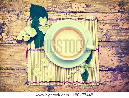 A cup of jasmine tea and jasmine flowers on an old wooden surface. Green tea. A refreshing and healthy drink. Selective focus. Retro style