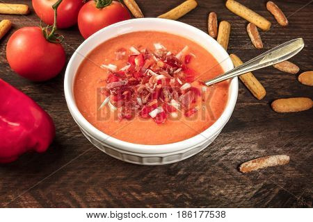 Photo of gazpacho, traditional Spanish soup, with tomatoes, red bell pepper, garlic cloves, and typical bread sticks, garnished with jamon and onion, on dark rustic background with place for text