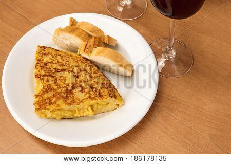 A photo of a tortilla, traditional Spanish potato omelette, with white bread, glasses of red wine, and a place for text. Typical tapas