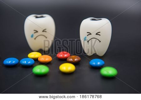 Model Cute toys teeth and colorful candy in dentistry on a black background.