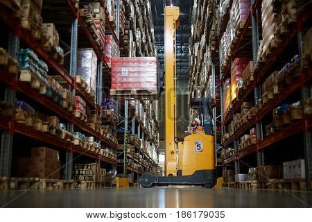 Forklift truck standing in aisle between large-scale shelves