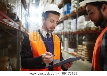 Worker in helmet and uniform reading list of shipped goods