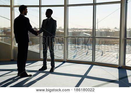 Two modern businessmen handshaking after making agreement