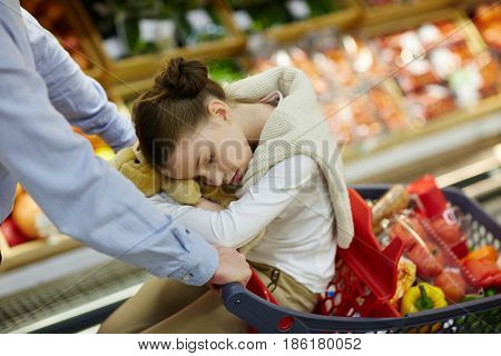Portrait of little tired girl falling asleep in shopping cart while parents buy groceries