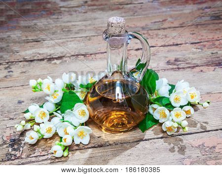 Jasmine oil concept spa with jasmine flowers on an old wooden surface. Aromatherapy. Retro style