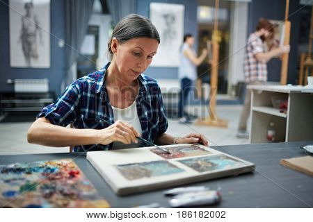 Portrait of mature student working in art studio painting pictures looking focused and concentrated