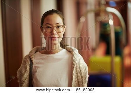 Portrait of smiling Asian woman standing in hotel hall with bags looking at camera