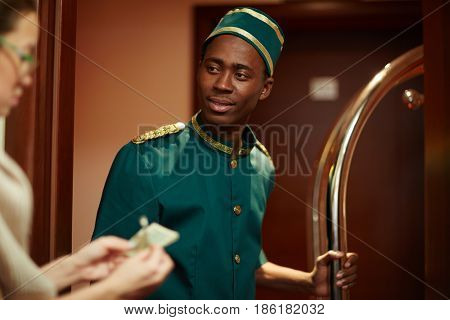Portrait of young African boy working as bellhop in luxury hotel, getting tip from woman guest for delivering luggage to room