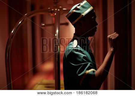 Side view portrait of African bellboy knocking on hotel room door delivering luggage in dim hallway