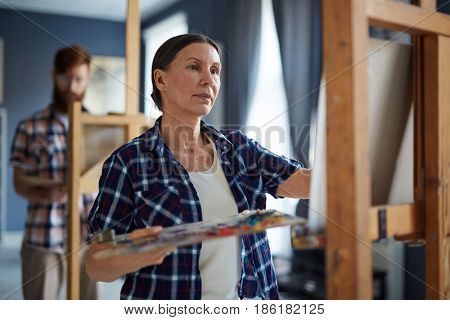 Portrait of elegant mature woman painting picture on easel standing in row of students in art class