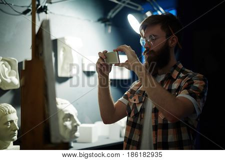 Portrait of contemporary bearded artist finishing his painting and taking photos of masterpiece with smartphone