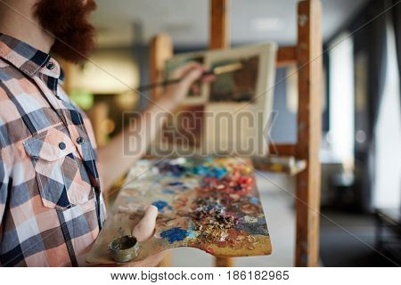 Closeup portrait of modern bearded artist painting picture on canvas using palette with canvas in art studio