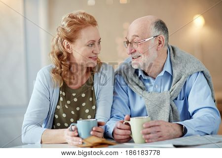 Cheerful and amorous mature man and woman having talk by tea