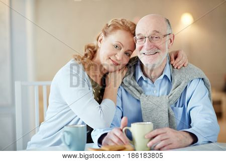Serene spouses looking at camera by cup of tea