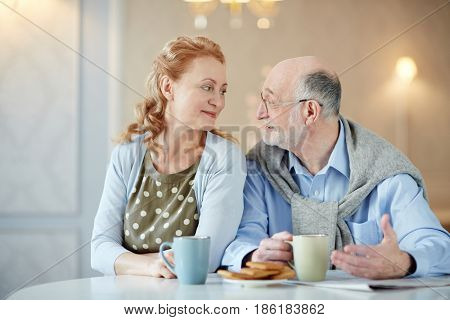 Amorous mature woman looking at her husband while listening to him by cup of tea