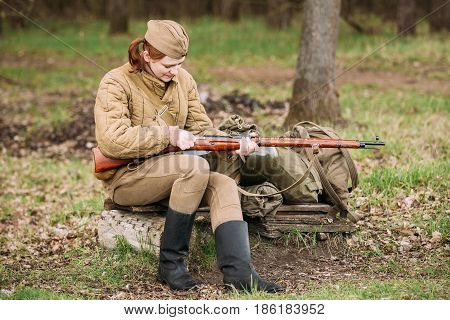 Pribor, Belarus - April 23, 2016: Young Woman Re-enactor Dressed As Russian Soviet Infantry Soldier Of World War II In Forest