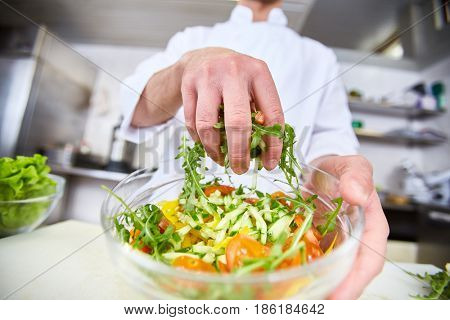 Chef mixing salad ingredients in bowl