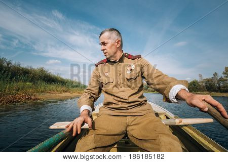Dyatlovichi, Belarus - October 1, 2016: Man Reenactor Dressed As Russian Soviet Red Army Infantry Soldier Of World War II Make Crossing Of River On A Boat