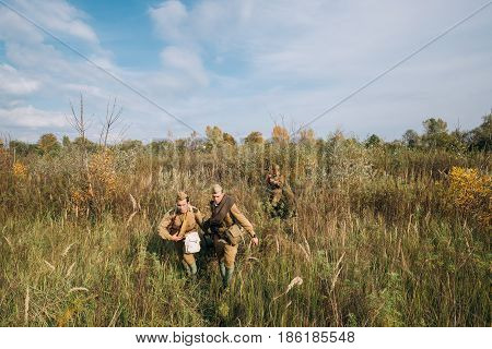 Dyatlovichi, Belarus - October 1, 2016: Reenactors Dressed As Russian Soviet Red Army Soldiers Of World War II Walking With With Maxim's Machine Gun Weapon In Autumn Meadow Forest