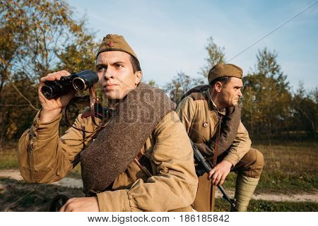 Dyatlovichi, Belarus - October 2, 2016: Young Man Reenactor Dressed As Russian Soviet Red Army Infantry Soldier Of World War II Looking At An Old Army Military Binoculars.