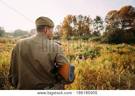 Dyatlovichi, Belarus - October 2, 2016: Reenactor Dressed As Russian Soviet Red Army Soldier Of World War II Hidden Sitting And Aiming Rifle Weapon In Grass In Autumn Forest