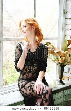 Woman in black lace peignoir sitting on the window sill. Boudoir portrait.