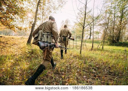 Two Re-enactors Dressed As Russian Soviet Red Army Soldiers Of World War II Hidden Running To Enemy Positions In Autumn Forest During Historical Reenactment.