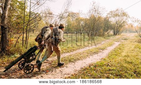 Reenactor Dressed As Russian Soviet Red Army Soldier Of World War II Running With Machine Gun In Autumn Forest At Historical Reenactment