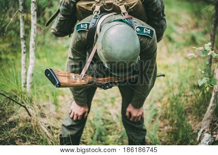 Tired Unidentified Re-enactor Dressed As German Wehrmacht Infantry Soldier In World War II Trying To Catch His Breath At Rest In Forest In Summer Day.