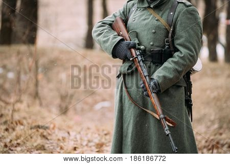 Close up of German military ammunition of a German soldier at World War II. Warm autumn clothes, soldier's overcoat, gloves, rifle