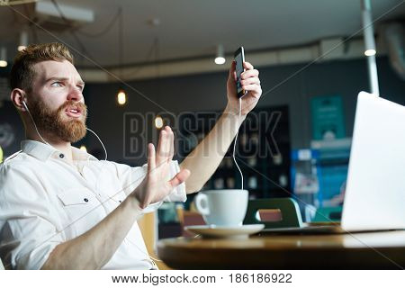 Modern man with smartphone and earphones communicating through video-chat in cafe