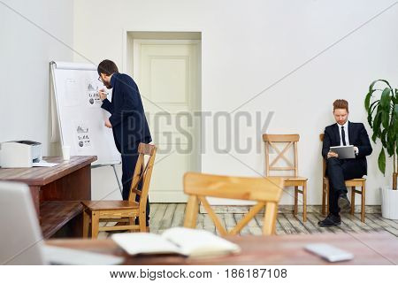 Business coach analyzing data on whiteboard while preparing for seminar