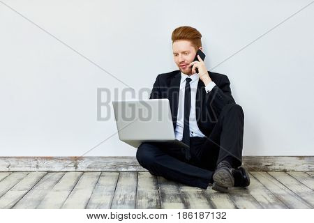 Salesman with laptop speaking to client on cellphone