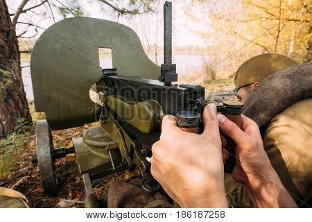 Reenactors Dressed As Russian Soviet Red Army Soldiers Of World War II Hidden Sitting With Machine Gun Weapon In An Ambush In Autumn Forest