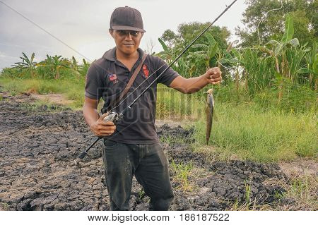 Labuan,Malaysia-May 7,2017:Fisherman holding a fresh snakehead fish caught in Labuan river,Malaysia.The snakeheads are members of the freshwater perciform fish family Channidae,native to parts of Africa & Asia.